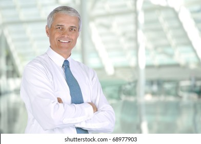 Smiling middle aged businessman standing in the lobby of a modern office building. Man is wearing white shirt and necktie with his arms crossed. Horizontal Format.