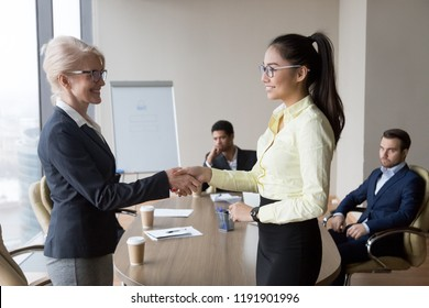 Smiling middle aged businesswoman handshake Asian employee congratulating with promotion, happy female boss shake hand of millennial woman worker greeting with good work results. Reward concept