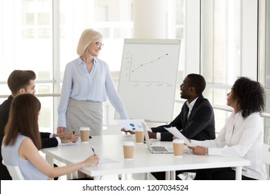 Smiling middle aged businesswoman stand holding business meeting with young colleagues, friendly female mature boss talk with employee, diverse millennial workers briefing in office discussing project