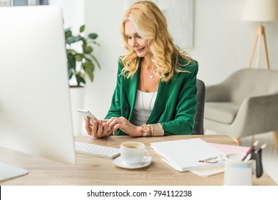 smiling middle aged businesswoman using smartphone and desktop computer at workplace