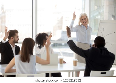 Smiling middle aged coach leader mentor raising hand with diverse mixed race team people engaging in voting, asking questions, supporting teambuilding, making group decision at employees training