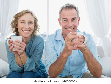 Smiling middle aged couple sitting on the couch having coffee looking at camera at home in the living room