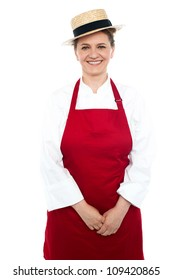 Smiling middle aged female chef wearing hat and dressed in white and red uniform