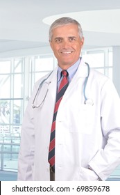 Smiling Middle Aged Male Doctor in Lab Coat with Stethoscope standing in a modern medical facility.