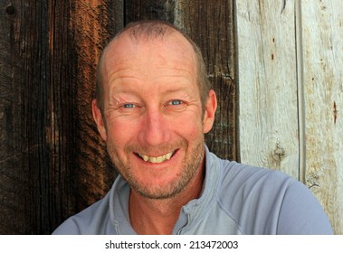 Smiling middle aged man with a barn wood background.