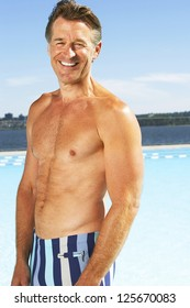Smiling middle aged man in good shape posing by the swimming pool