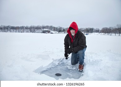A smiling middle aged man ice fishing on a snowy lake in Minnesota during the winter