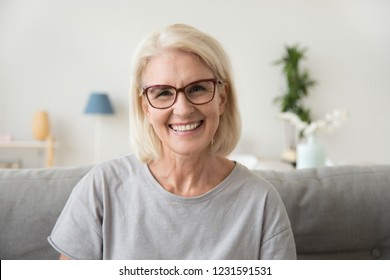 Smiling middle aged mature grey haired woman looking at camera, happy old lady in glasses posing at home indoor, positive single senior retired female sitting on sofa in living room headshot portrait