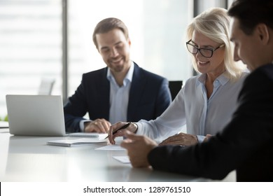 Smiling middle aged older businesswoman signing paper contract at group meeting, happy mature senior woman client puts signature on business document fills form making agreement deal, getting hired