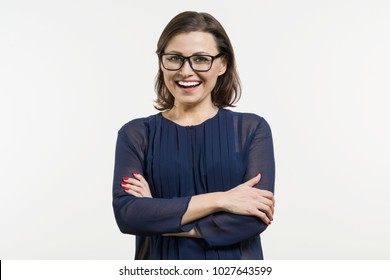 Smiling middle aged woman with folded arms on white background.
