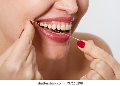 Smiling middle aged  woman with ideal strong white teeth, teethcare. Selective focus. Healthcare, stomatological concept for dentists. Cleaning teeth with tooth thread.