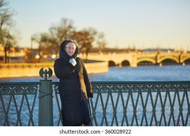 Smiling middle aged woman on the bridge in St. Petersburg, Russia on a sunny winter day