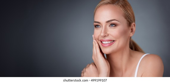 Smiling middle aged woman satisfied with her nature beauty