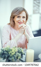 Smiling Middle Aged Woman Sitting At Table. Having Laptop Before Her. Going To Make Online Shopping.