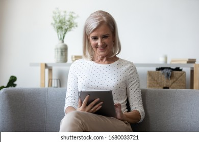Smiling middle aged woman sitting on comfortable sofa with computer digital tablet. Happy older generation lady shopping online in internet store at home, using electronic device for communication.