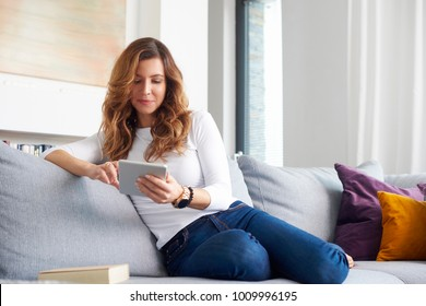 A smiling middle aged woman using digital tablet while relaxing on sofa at home.
