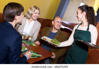 Smiling middle class people enjoying food, waitress taking order