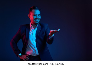Smiling middle-aged Asian businessman looking at invisible innovative product on his hand
