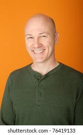 Smiling middle-aged bald Caucasian man on orange background