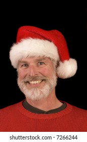 Smiling middle-aged bearded man in a santa hat and red sweater over a black background