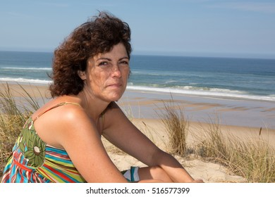 Smiling middle-aged brunette woman on the beach