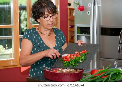 a smiling middle-aged brunette woman preparing meal