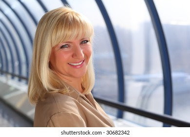 Smiling middle-aged businesswoman on bridge