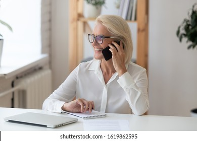 Smiling middle-aged businesswoman sit at desk smiles talking on smartphone looking out the window enjoy pleasant conversation with client, female sales manager makes successful profitable deal concept
