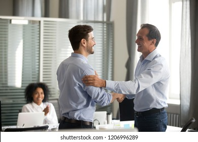 Smiling middle-aged ceo promoting motivating worker shaking hands congratulating with achievement promising respect bonus thanking for good work, team applauding, employee reward recognition concept