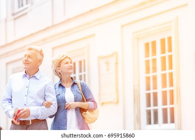 Smiling middle-aged couple standing with arm in arm outside building