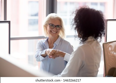Smiling middle-aged female employee shake hand greeting get acquainted with colleague at workplace, positive businesswoman handshake introduce to woman coworker in office. Cooperation concept