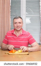 A smiling middle-aged man cutting vegetables in the kitchen