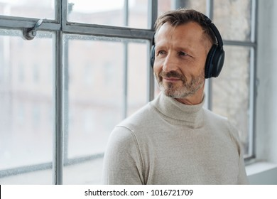 Smiling middle-aged man listening to his music as he leans against a windowsill turning to look outside
