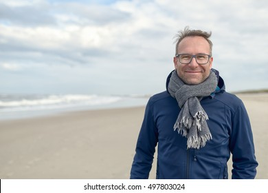 Smiling middle-aged man wearing glasses and a knitted woollen scarf standing on a deserted autumn beach on a cloudy day with copy space