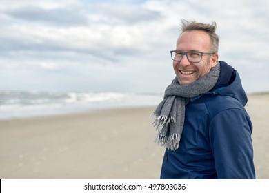 Lächelender Mann mittleren Alters mit Brille und einem Strickerschal, der an einem bewüsteten Tag auf einem menschenleeren Herbststrand steht und Kopienraum hat