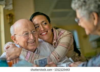 Smiling middle-aged woman embraces her cheerful grandfather as her elderly grandparents play cards together at the kitchen table.