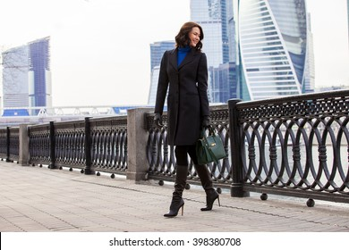 smiling middle-aged woman in a fashionable dark coat and a green handbag walking on the promenade. copy space