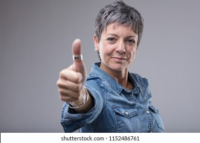 Smiling middle-aged woman giving a thumbs up gesture of approval and success or votes for yes isolated on grey with copy space