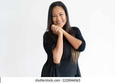 Smiling middle-aged woman with her hands clasped. Lady looking at camera. Tenderness concept. Isolated front view on white background.