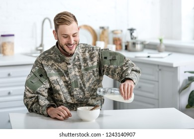 Smiling military man pouring milk in bowl with cornflakes