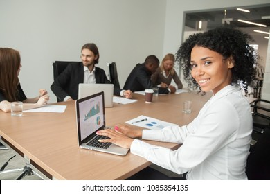 Smiling millennial african businesswoman looking at camera at meeting, female afro american marketing manager using laptop at group office briefing, young black project sales professional portrait