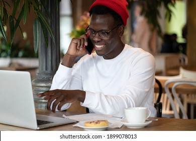 Smiling millennial Afro-American hipster man wear red hat talking on cellphone, remotely online working on laptop computer in cafe during lunchtime.