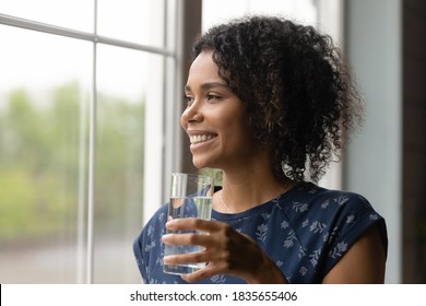 Smiling millennial biracial woman look in distance hold glass of water drink clean clear mineral aqua for body refreshment. Happy African American girl follow healthy lifestyle. Hydration concept.