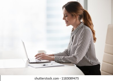 Smiling millennial businesswoman using laptop chatting with friends, happy female boss typing messages on computer, texting with boyfriend or lover at workplace, woman distracted from work