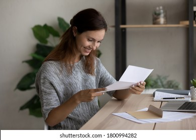 Smiling millennial Caucasian girl sit at table at home read good news in postal letter correspondence, happy young woman open envelope feel excited get pleasant message or notice in post paperwork