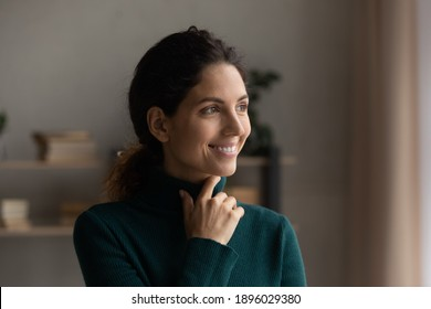 Smiling millennial Caucasian woman look in distance window dreaming or planning success. Happy young female thinking or pondering, visualize or imagine opportunity at home. Visualization concept.