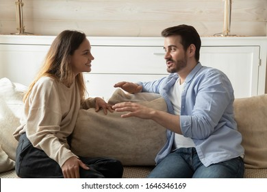 Smiling millennial couple sit on sofa in living room involved in interesting pleasant conversation at home, happy young man and woman talk chat relaxing on couch, enjoy romantic weekend or date
