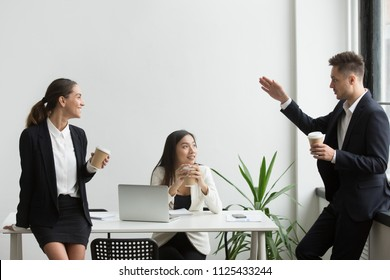 Smiling millennial diverse people chatting during coffee break together, friendly multi-ethnic colleagues talking listening to coworker telling story in office room, good team relations concept