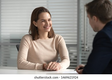 Smiling millennial female candidate speak with male HR manager at work interview in office, positive happy woman chat with recruiter or employer at job talk make good first impression. Hiring concept