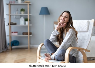 Smiling millennial girl sitting in a cozy chair at home. Lifestyle female portrait indoors.
